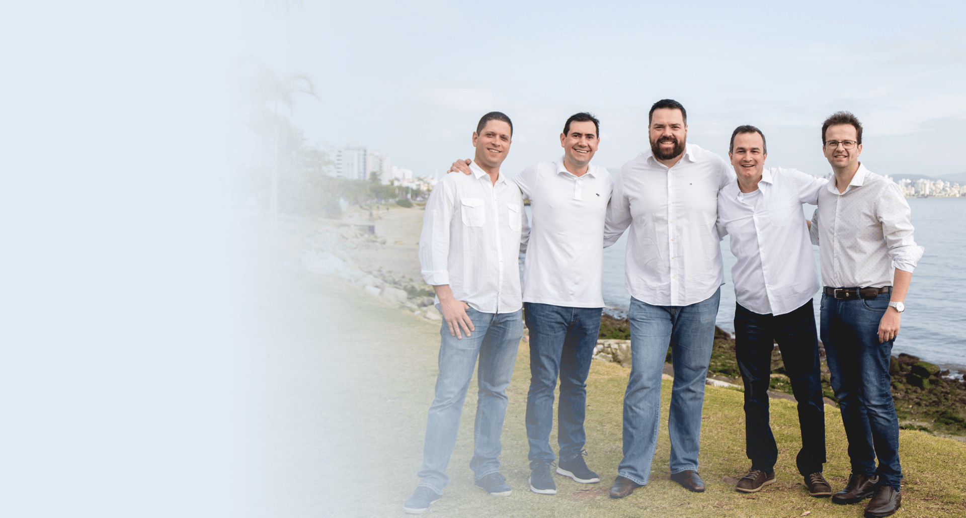 Doutores Gustavo, Daniel, Acklei, Jalmir e Rafael vestidos de camisas brancas, estão reunidos em região costeira de Florianópolis. Todos sorriem. Há um degradê para branco no lado esquerdo da imagem.